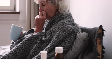 weefsel : Older ill woman holding handkerchief blowing nose sitting in bed at home with cold remedy. Sick elder lady got flu virus having grippe symptom. Seniors respiratory diseases and antiviral drugs concept