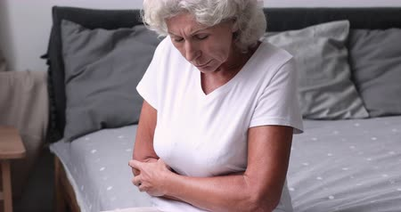 беспорядок : Sick senior woman feeling stomach ache concept sitting on bed. Upset older grandma holding belly suffering from abdomen tummy pain in morning. Elderly person gastritis health problem. Close up view Стоковые видеозаписи