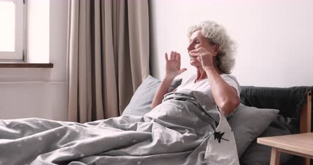 desperto : Happy fresh vivacious 70s older lady waking up alone in cozy comfortable bed. Smiling healthy retired senior woman stretching sitting in bedroom feeling full of energy enjoying good morning concept