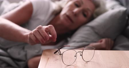 optický : Senior adult woman waking up in the morning taking and wearing optical glasses. Old grandmother having bad weak sight, elderly vision problem. Visually impaired elder person concept. Close up view