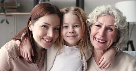milující : Smiling intergenerational women family embracing bonding together. Cute little child girl granddaughter hugging young mum and happy old grandmother, looking at camera. 3 three age generations portrait Dostupné videozáznamy