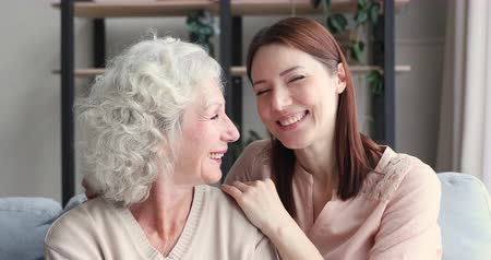 milující : Relaxed happy young adult daughter embracing old mother and laughing together. Smiling grown granddaughter hugging senior grandma looking at camera at home. Two 2 age generations women family portrait