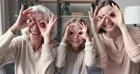 três pessoas : Happy funny multigenerational family have fun make binoculars glasses. Cheerful old grandma, young mother adult daughter and small child granddaughter laugh look at camera. 3 women generation portrait