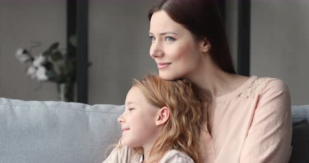 milující : Loving single mother embracing kid daughter looking away. Young smiling foster care parent mum hugging adopted child girl sitting on sofa dreaming of good future enjoying sweet moment of love concept. Dostupné videozáznamy