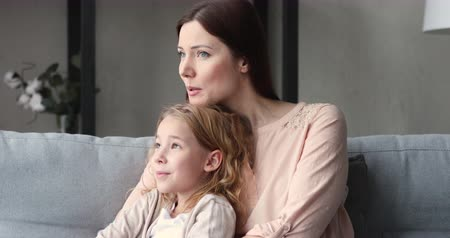 milující : Dreamy single mom hugs cute daughter talking relaxing on sofa. Loving young mother embracing kid girl looking away thinking of future enjoys warm relationship of foster care parent and child at home.
