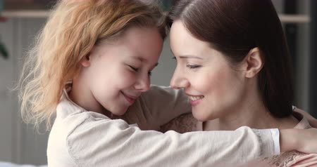 нежный : Cute child daughter and adult mommy cuddling looking at camera. Affectionate young mother embracing small smiling kid girl, hugging and bonding. Happy single foster parent and child close up portrait