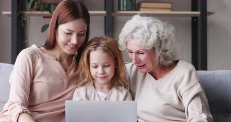 мультфильмы : 3 three generations women family laughing watching funny videos on laptop. Happy old grandma, young mother adult daughter and small granddaughter using computer having fun relaxing on sofa at home. Стоковые видеозаписи