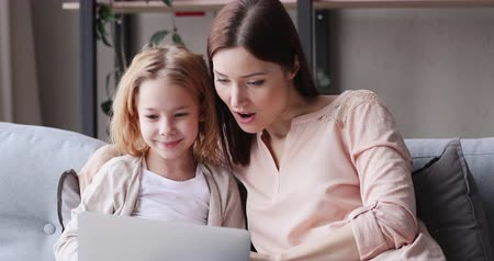 премия : Excited young mother and kid girl look at laptop computer screen feel winners. Amazed mom with child daughter watching online game winning shopping sale discount. Family ecommerce success concept