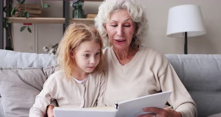 sprookje : Senior granny holding fairytale book hugging kid girl granddaughter sitting on sofa. Happy old grandmother nanny teaching grandkid learning reading at home. Grandparent and grandchild activity concept