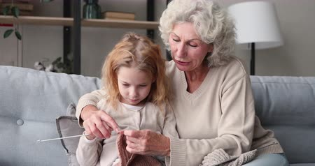 babysitter : Senior 70s grandmother teaching cute 6-7 years old granddaughter knitting together. Happy two 2 generation family doing handcraft activity. Grandkid learning new skills having fun with grandma at home