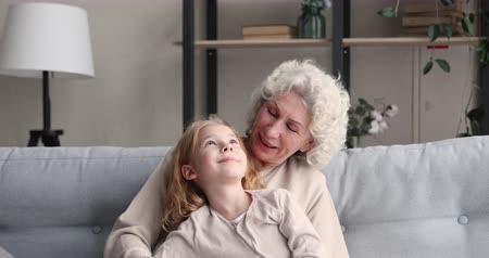 milující : Relaxed senior grandma hugging and talking with school child granddaughter at home. Cute small girl grandkid bonding having trust conversation with old grandparent enjoying sweet warm moment together.