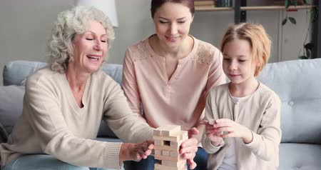 внучка : Multigenerational female family playing jenga board game together. Happy 3 three generations of women - old senior granny, young mother and small child granddaughter enjoying leisure activity at home.