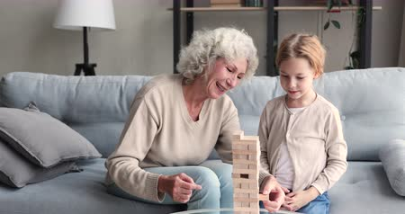 babysitter : Carefree elderly grandma and small granddaughter playing jenga taking blocks out of wooden tower. Happy 2 generations family old grandmother with cute grandkid having fun enjoying board game at home. Stock Footage