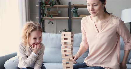 koncentracja : Cute funny small school girl daughter playing jenga with young mom. Female nanny or adult parent mother having fun learning board game with kid. Mum and child building tower of wooden blocks at home