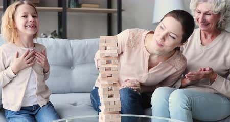 mãe : Happy three 3 age generations women family having fun playing jenga board game together. Cheerful young adult mom laughing enjoying funny leisure activity with old grandma and kid grandchild at home.