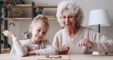 nanny : Happy 2 two age generations family playing board game at table. Smiling old senior grandma teaching cute school girl granddaughter learning draughts. Grandparent and grandkid enjoying wooden checkers