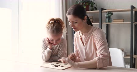 concentrando : Small 6-7 years daughter and young mom playing checkers at home table. Cute child girl having fun with mother or nanny enjoying draughts board game. Parent and kid leisure hobbies activities concept Vídeos