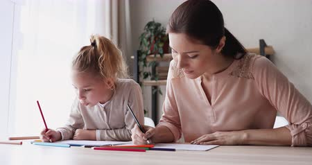 puericultura : Happy mum helping kid daughter drawing colored pencils at home. Cute smart school child girl playing with young mom or nanny sitting at table. Parent and kid creative art educational activity concept