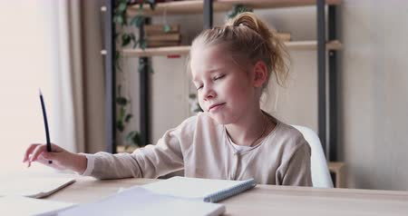 жесткий : Funny elementary school child girl studies alone talks to herself feels bored, annoyed or tired. Cute lazy 6-7 years kid having difficulty with homework at home. Problem in children education concept