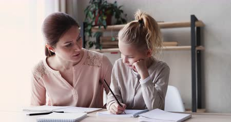 書く : Cute small 6-7 years kid daughter learning writing with young mom tutor. Adult parent mother teaching school child girl helps with homework studying sitting at home table. Children education concept