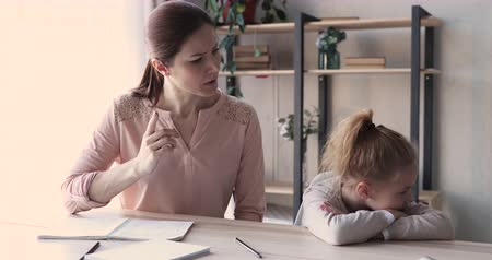 most : Angry young mom scolding stubborn lazy school girl about undone homework. Mad adult mother shouting at small kid ignore punishment at home. Parent disciplining child daughter for education concept