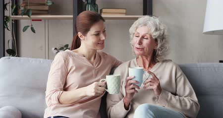 честный : Happy 2 two age generations women family chatting drinking tea at home. Relaxed old elder mother and young adult daughter talking and laughing sitting on sofa, resting in cozy living room together. Стоковые видеозаписи