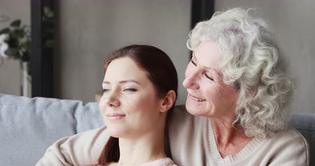 milující : Relaxed loving senior mother embracing young daughter and talking resting on sofa. Happy old grandma bonding with adult granddaughter chatting enjoying moments of understanding and warm relationship.