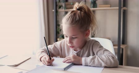 koncentracja : Focused cute smart school child girl studying alone doing writing homework in exercise book sitting at home table. 6-7 years kid learning handwriting making note. Children elementary education concept