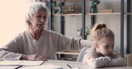 desobediente : Worried senior grandma scolding lazy small grandchild schoolgirl demanding discipline in homework. Angry old grandmother teacher punishing disobedient granddaughter must learn school education concept Vídeos