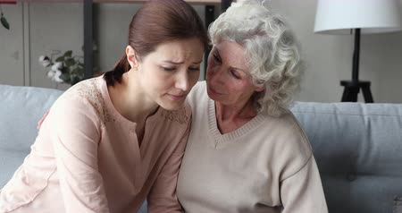 konzol : Empathic worried senior mother comforting sad crying young daughter. Caring elderly grandma helping upset adult granddaughter sharing problem. Two age generations women psychological support concept Stock mozgókép