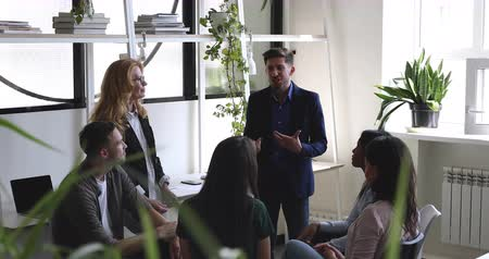 diverso : Happy multiracial colleagues listening to positive team leader in modern office. Smiling male boss businessman explaining project details to interested older and younger mixed race teammates. Stock Footage