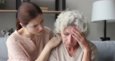 把握 : Worried young daughter supporting upset senior mother sharing problem. Caring adult granddaughter helping sad old grandmother encouraging elder grandparent giving empathy, care and compassion concept. 動画素材