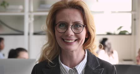 speaker : Head shot close up older smiling businesswoman professional coach trainer teacher in eyeglasses looking at camera. Happy middle aged company female red-haired ceo executive boss posing for photo. Stock Footage