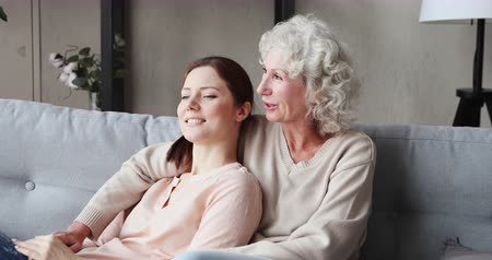 rada : Happy serene old grandmother and young grown granddaughter bonding chatting at home. Relaxed two age generation women family lounge on couch. Senior mum embracing adult daughter enjoys peaceful talk. Wideo
