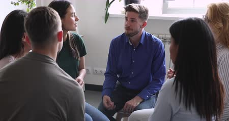 oturum : Diverse people sitting in circle, sharing personal problems at psychotherapy session. Male psychologist therapist helping multiracial younger and older patients at group therapy, rehab concept.