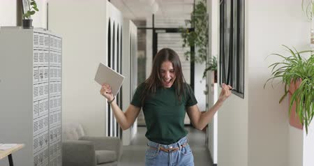 jest : Overjoyed young company employee celebrating company success, personal achievement, good news receiving, salary increasing, rewarding job promotion, shouting screaming, making yes gesture in office.