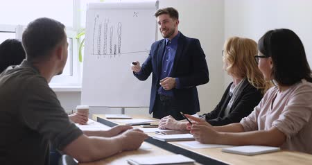 тренер : Smiling confident male speaker trainer coach presenting marketing plan on whiteboard to positive diverse coworkers in modern office. Smart business people taking part in educational lecture workshop.