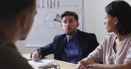 тренер : Focused young businessman sharing business ideas with colleagues at brainstorming meeting. Confident team leader developing marketing strategy after analyzing paper reports with coworkers in office.