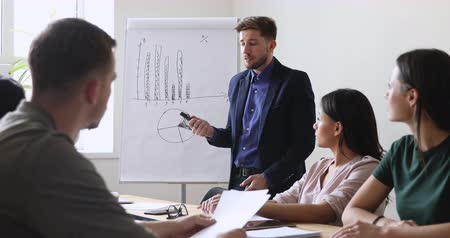 warsztat : Focused team leader presenting marketing plan to interested multiracial coworkers. Serious smart male speaker boss executive explaining development strategy to motivated mixed race employees.