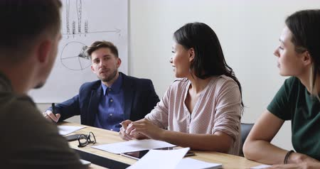задумчивый : Young multiracial people discussing project details at business meeting in office. Pensive employee sharing ideas with motivated mixed race coworkers partners, sitting together at office desk.