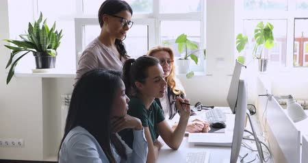 engaged : Successful female team leader explaining new corporate computer software to young and mature mixed race colleagues in office. Happy diverse employees looking at monitor, discussing project results.
