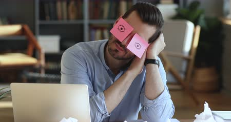 deprived : Funny lazy office worker napping at workplace covering eyes with sticky notes. Inefficient tired male employee pretends working sleeping with stickers on face sits at desk. Cheating to sleep concept Stock Footage