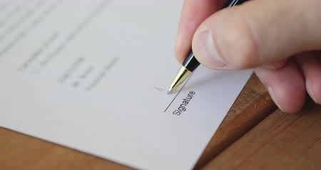 dokumentum : Businessman customer putting written signature on business paper. Male customer or buyer holding pen in hand writing signing document form giving consent concept. Legal authorization, close up view Stock mozgókép