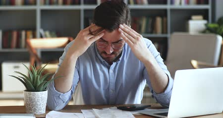 makbuz : Depressed desperate man feeling worried about financial problem doing paperwork. Stressed businessman looking frustrated thinking of money debt, budget loss, bankruptcy sitting at home office desk. Stok Video