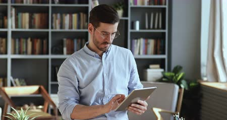 usuario : Young businessman using digital tablet computer online app business software. Male professional entrepreneur holding tech device working on modern pad gadget managing tasks standing at home office. Archivo de Video