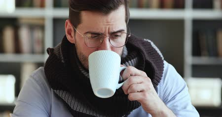 urlop : Unhealthy ill man blowing running nose drinking hot tea. Sick businessman wear scarf holding tissue having flu symptom caught cold sitting at home office. Virus seasonal disease health problem concept