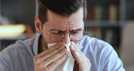 urlop : Ill young man having allergy symptoms blowing running stuffy nose in tissue. Unhealthy businessman suffering from sniffles, allergic rhinitis concept sitting at home or in office. Close up view