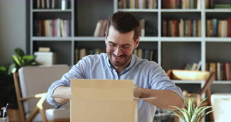 postpakketje : Smiling young man customer opening parcel cardboard box sitting at home office desk. Happy consumer unpacking postal shipping delivery satisfied with good purchase. Fast post shipment service concept