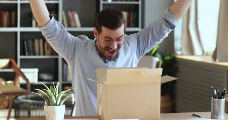 postpakketje : Excited man customer winner opening cardboard parcel box receiving gift sitting at home office desk. Overjoyed male consumer shopper unpacking postal delivery celebrating good online purchase concept. Stockvideo