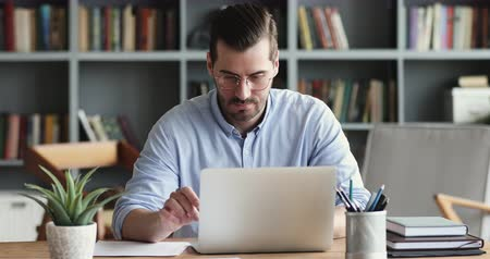 экономический : Focused business man entrepreneur typing on laptop doing research. Young male professional using computer sitting at home office desk. Busy worker freelancer working on modern tech notebook device. Стоковые видеозаписи